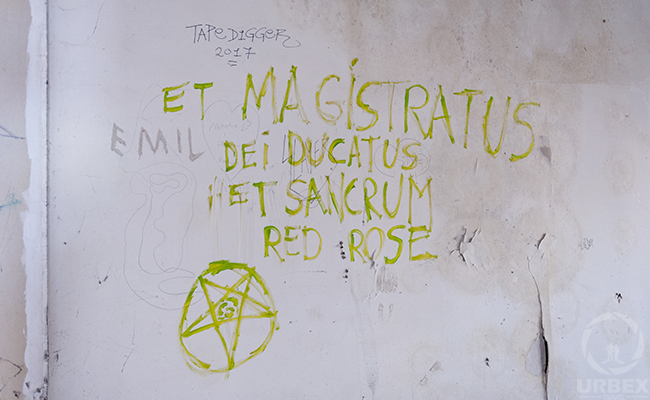 satanic symbols on the wall in an abandoned building