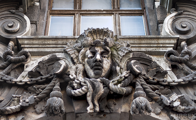 a mask on the facade of an abandoned palace in Budapest
