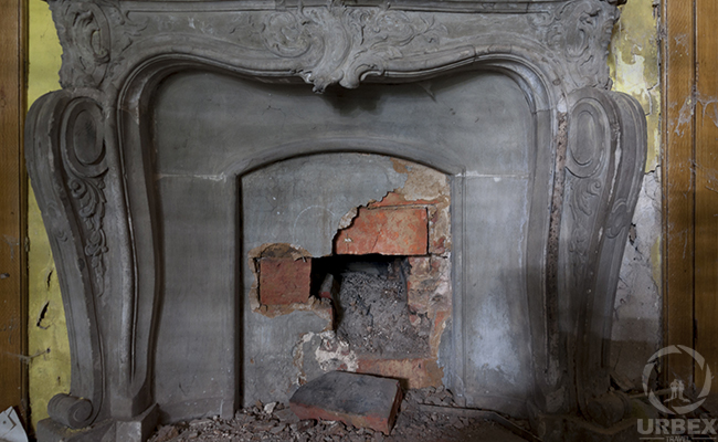 decaying fire place in an abandoned mansion