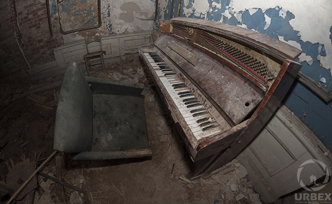 an old piano in an abandoned mansion