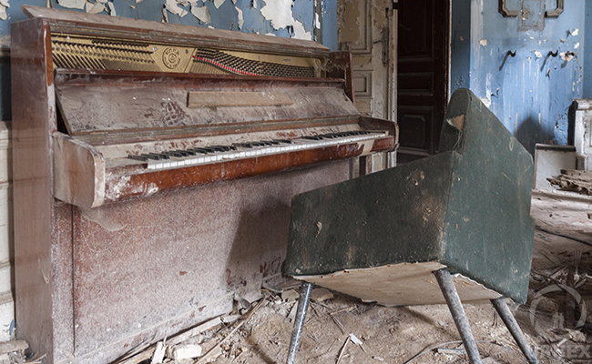 an old piano in an abandoned palace