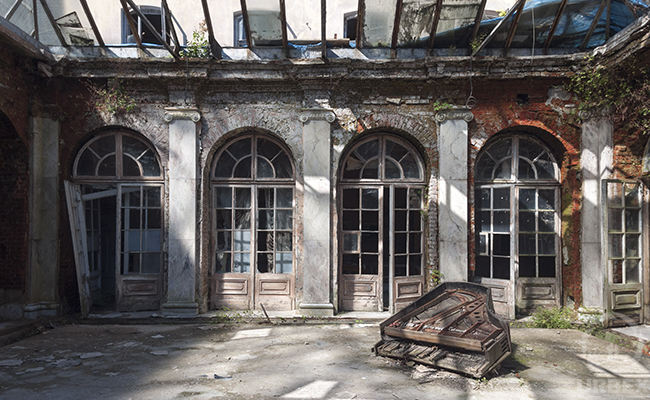 an old piano on a sunny patio of an abandoned palace
