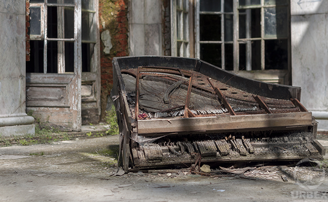 decaying piano in an abandoned mansion